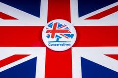 Crachá do partido conservador sobre a bandeira BRITÂNICA imagens de stock