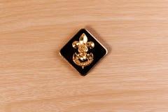 Crachá dos escuteiros de menino do vintage na tabela de madeira Imagens de Stock Royalty Free
