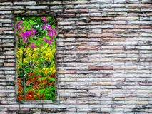 Crack brick wall and  purple red yellow flower green tree Royalty Free Stock Image