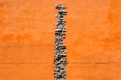 Crack of bricks in orange wall Stock Photo