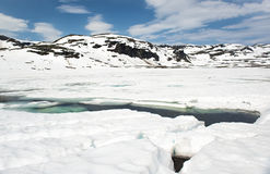 The crack in the ice, the snow-covered lake and the mountains, Norway Royalty Free Stock Photo