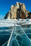 Crack line runs to Shaman rock at Olkhon island,Baikal lake. Crack line on surface of frozen Baikal lake runs to Shaman rock at Olkhon island on the sunny day Stock Images