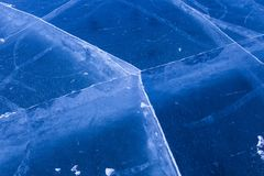 Crack lines network on thick frozen surface of Baikal lake, Russia stock photo