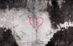 Crack in red heart sharp by hand write of old white concrete wal Royalty Free Stock Images