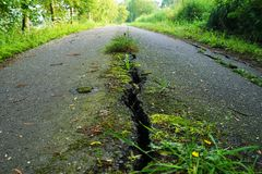 Crack in a road in summer. Wide crack in a road in summer stock photo