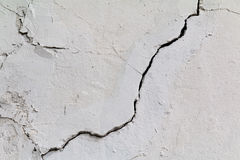 Crack. Texture of old painted white plaster. Cracked wall. stock photos