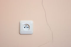 A crack in the wall. A crack in the wall and the power outlet Royalty Free Stock Image