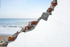 Crack white bricks wall with ocean beach and blue sky Royalty Free Stock Photos