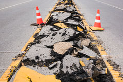 Cracked asphalt road with marking lines and safty cones Stock Photo