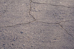 Cracked asphalt road texture. Gray cracked asphalt road texture. Structured background Stock Images