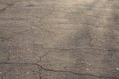 Cracked asphalt road texture. Gray cracked asphalt road texture. Structured background Royalty Free Stock Photography