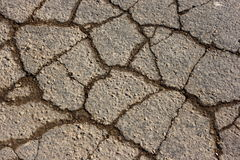 Cracked Asphalt Texture. A close-up view of an asphalt road, cracked and broken from the weather Royalty Free Stock Photo