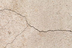 Cracked beige wall texture. Yellow sand stone with a crack Royalty Free Stock Photography