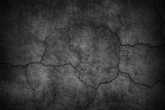 Cracked black concrete wall, gloomy cement texture background. Black cement wall. Dark texture of cracked concrete Royalty Free Stock Photography