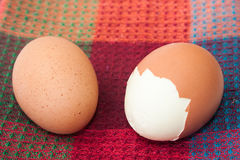 Cracked boiled egg on the kitchen tablecloth Royalty Free Stock Photo