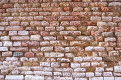 Cracked brick wall. Old abandoned cracked wall with old colorful bricks on different levels Royalty Free Stock Images
