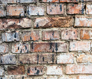 Cracked brick wall stained with black tar Stock Photo