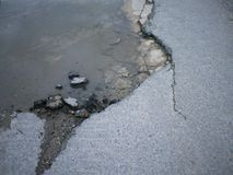 Cracked and broken asphalt pothole with water on the surface of stock images