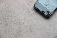 Cracked cell phone on the floor. A cracked cell phone on the floor royalty free stock photography