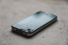 Cracked cell phone on the floor. A cracked cell phone on the floor stock photos