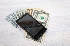 Cracked cellular phone and American money on white Royalty Free Stock Image