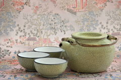 Cracked ceramic teapot and three cups Stock Images