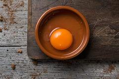 Cracked chicken egg on a wooden table. High-angle shot of an earthenware plate with a cracked chicken egg on a rustic wooden table Stock Images