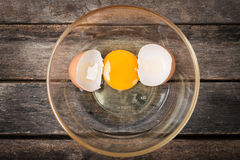 Cracked chicken egg with yolk and egg shell on dish, wooden background Stock Photos