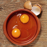 Cracked chicken eggs on a wooden table Royalty Free Stock Photos