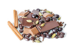 Cracked chocolate bar, dragee and  spices  on white Stock Photos