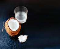 Cracked coconut  with Coconut Milk in a Glass. Coco nut cut in h Royalty Free Stock Photos