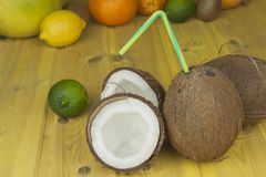 Cracked coconut on yellow wooden table. Preparing coconut refreshing drink. Tropical drink. The table at the beach bar. Royalty Free Stock Image