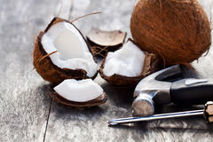 Cracked   coconuts and hammer on old wooden table Royalty Free Stock Photo