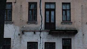 Cracked collapsed house. Crack in the wall foundation of an old house closeup