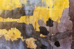 Cracked concrete wall. Bright yellow painted wall with dark spots of plaster. Grunge background Royalty Free Stock Photography