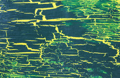 Cracked dark green paint on the dark yellow surface Stock Photo