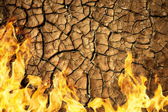 Cracked dry soil of earth texture with fire flames. Stock Image