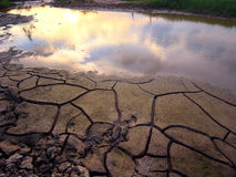 Cracked earth. With sunset sky Stock Photos