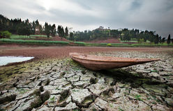 The dry river. Cracked earth with boat , metaphoric for climate change and global warming, more and more rivers are drying out Royalty Free Stock Photo