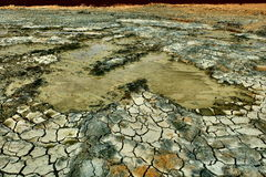 Cracked earth. Colored dried cracked dirt field Royalty Free Stock Image