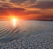 Cracked earth seacoast on sunset background Stock Image