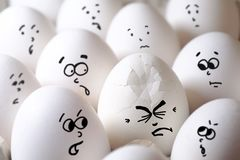 Cracked egg among all eggs. One cracked egg between all normal eggs stock images