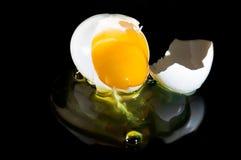 Cracked egg on black. Raw egg on black background Stock Photos