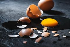 A cracked egg with an egg shell, egg yolk and egg white on white royalty free stock photography