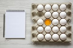 Cracked egg among other chicken eggs in carton egg box with notebook, top view. stock photography