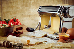 Cracked eggshell with pasta in press with tools Royalty Free Stock Photography