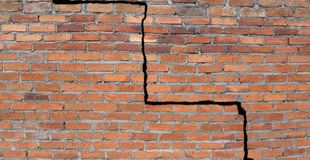 Cracked foundation. Large crack in a brick wall building foundation royalty free stock photo