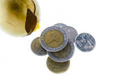 Cracked golden egg and Thai coins isolated. On white Royalty Free Stock Photo