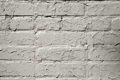 Cracked gray paint on a brick wall. Grunge background Royalty Free Stock Image
