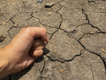 Cracked ground and angry fist hand Royalty Free Stock Photos